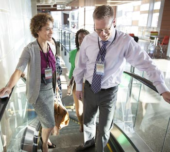 Two business professionals riding up an escalator.